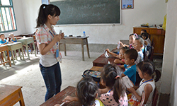 Female volunteer stands in front of children and teaches at school in China