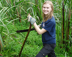 Female volunteer poses with bamboo stick