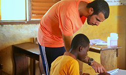 Male volunteer leans over and helps a child with homework