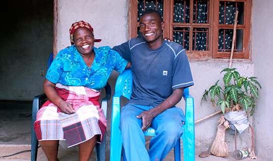 Mother and son sit outside house in Mozambique