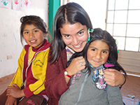 Female volunteer hugs two children and smiles at camera