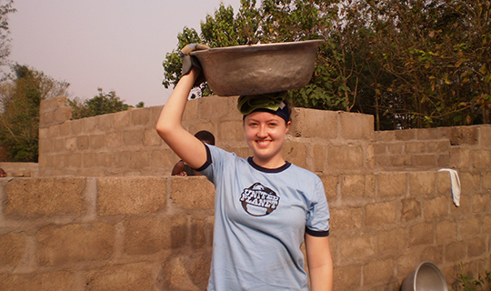 Girl wearing United Planet tshirt holds bowl ontop of her head in Ghana