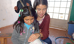 Female volunteer reads to young Peruvian child