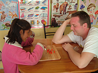 Male volunteer plays game with Peruvian child