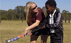 Female volunteer teaches young south african boy how to hold a hockey stick