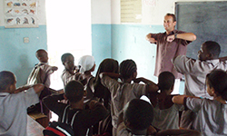 Male volunteer stands in front of class and teaches in Tanzania