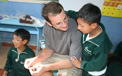 Male volunteer teaching young Ecuadorian child