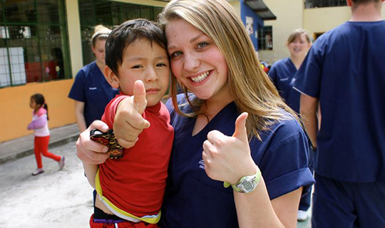 Dental volunteer smiles and gives thumbs up