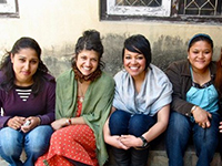 Female volunteers sit and smile in Nepal