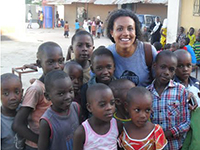 Female volunteer smiles with group of children in Tanzania