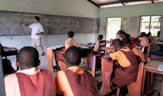 Volunteer in a white shirt teaching in front of a chalkboard